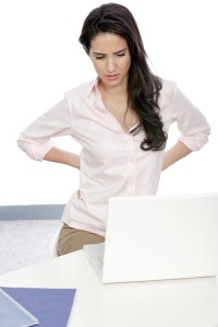 Woman sitting at her desk holding her back in pain